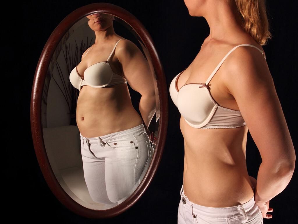 Homöopathie bei Essstörungen bietet wertvolle Hilfe (Frau vor Spiegel). © RioPatuca Images / Fotolia.com