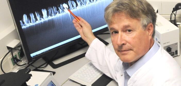 Prof. Dr. Manfred Köller zeigt die Vergrößerung einer Titanoberfläche mit einer speziellen Nanosäulenstruktur, die auf ihre antimikrobielle Wirkung getestet wird. © Volker Daum/Bergmannsheil