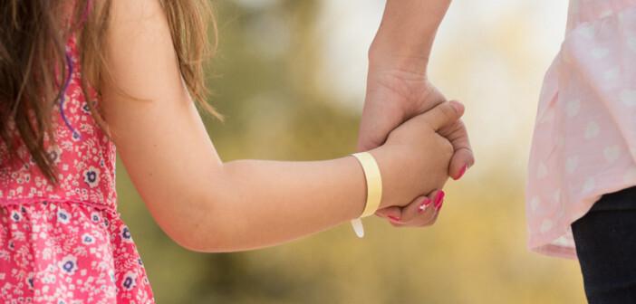 Zu Daylong kids: Kind mit Daylong UV-Sensor-Armband an der Hand.