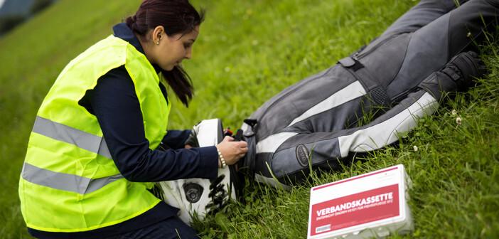 Motorrad-Unfälle in Österreich, Juni 2015. Helmabnahme. Eine Frau mit Warnweste nimmt vorsichtig den Helm ab. Im Vordergrund ist eine Verbandskassette zu sehen. © Österreichisches Rotes Kreuz