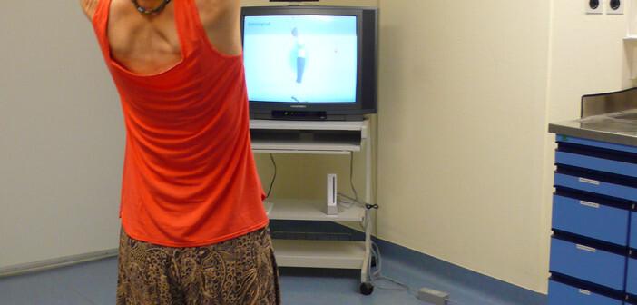 Anleitung zur Bewegungstherapie über eine Spielekonsole: Patientin bei einer Yoga-Übung. © Jan Zernicke / Charité