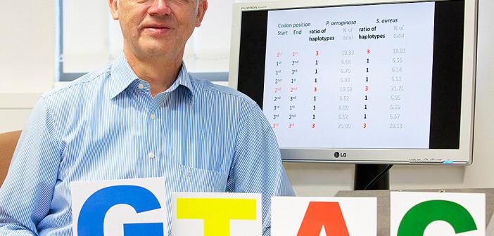 Professor Dr. Burkhard Tümmler mit den Anfangsbuchstaben der Basen Guanin, Thymin, Adenin und Cytosin, die Erbgut-Bestandteile sind. © MHH / Kaiser