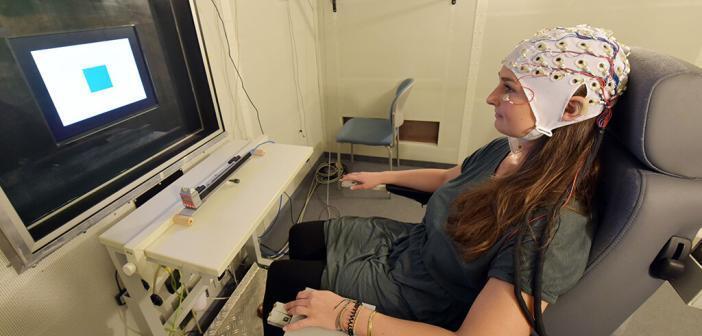 Eine unter Hypnose stehende Probandin muss auf verschiedene Symbole auf dem Bildschirm reagieren. Gleichzeitig wird per EEG ihre Hirnaktivität gemessen. © Jan-Peter Kasper / FSU